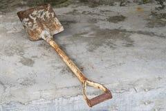 Alte verrostete Schaufel auf dem Zementboden stockfotografie