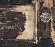 Alte verwitterte antike Schlag-obentäfelungstür mit abgebrochenem Schalenfarben- und Glaskristalltürknauf und rostiger Platte stockfotos