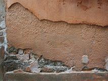 Alte verwitterte Backsteinmauer bedeckt, wenn rosa Zement abgezogen wird Stockbilder