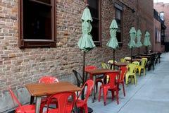 Alte, verwitterte Backsteinmauer mit bunten Tabellen und Stühle für das Außenseitenspeisen Stockfoto
