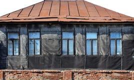 Alte verwitterte Backsteinmauer mit Fenstern Stockbild