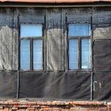 Alte verwitterte Backsteinmauer mit Fenstern Stockfoto