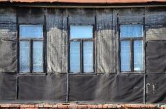 Alte verwitterte Backsteinmauer mit Fenstern Lizenzfreie Stockbilder