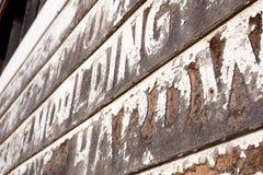 Alte verwitterte hölzerne Planken mit abgenutzter Beschriftung Stockbild