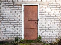 Alte verwitterte Scheunentür und -Backsteinmauer Stockfotografie