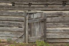 Alte verwitterte Tür auf einer antiken aufgegebenen Blockhauswand Stockfotografie