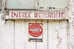 Alte verwitterte Tür mit Rot malte Text und Parkverbotsschild lizenzfreie stockfotografie