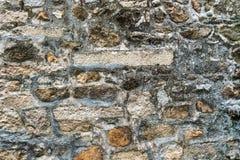 Alte verwitterte Wand konstruiert aus natürlichem Kopfstein Buntes horizontales Bild passend für Innenarchitektur, Hintergrund, W stockfoto