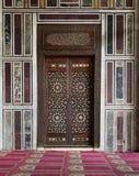 Alte verzierte Marmorwand mit einer historischen aufwändigen Holztür Lizenzfreie Stockbilder