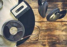 Alte Vinylaufzeichnung, Audiokassette, Bandspule und Kopfhörer Stockfotos