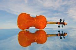 Alte Violine auf Spiegel- und Himmelraum Lizenzfreies Stockfoto