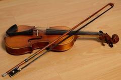 Alte Violine mit einem Bogen liegt auf Holzbank Stockfoto