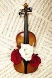 Alte Violine mit musikalischen Anmerkungen und Rosen Stockbilder
