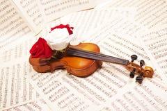 Alte Violine mit musikalischen Anmerkungen und Rosen Lizenzfreie Stockfotos