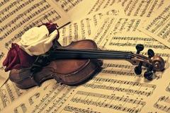 Alte Violine mit musikalischen Anmerkungen und Rosen Stockfoto