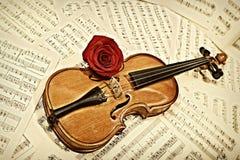 Alte Violine mit musikalischen Anmerkungen und stieg Lizenzfreies Stockbild
