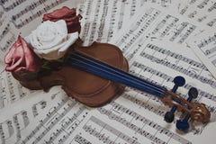 Alte Violine mit musikalischen Anmerkungen und stieg Lizenzfreie Stockfotos