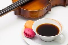 Alte Violine, Tasse Kaffee und traditionelles französisches buntes macaro Lizenzfreies Stockbild