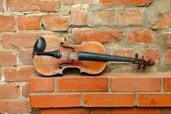 Alte Violine und leere Backsteinmauer Stockbild