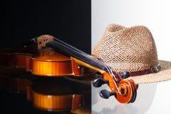 Alte Violine und Strohhut auf Schwarzweiss-Hintergrund Lizenzfreie Stockfotos