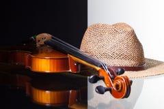 Alte Violine und Strohhut auf Schwarzweiss-Hintergrund Lizenzfreie Stockfotografie