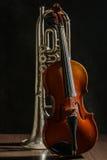 Alte Violine und Trompete auf einem schwarzen Hintergrund Stockfotografie