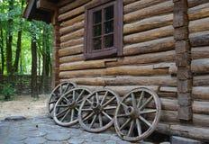 Alte Wagenräder gegen die Wand eines rustikalen Hauses Lizenzfreie Stockfotografie