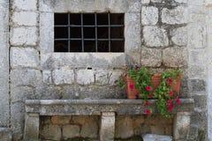 Alte Wand des Hauses mit einem Fenster und der Bank mit Blume Lizenzfreie Stockbilder