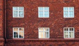 Alte Wand des roten Backsteins mit Fenstern in Helsinki Stockfotografie