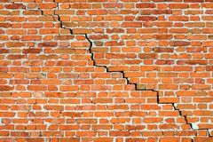 Alte Wand des roten Backsteins mit großem Sprung stockbild