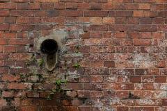 Alte Wand des roten Backsteins mit Rohr Lizenzfreie Stockfotografie