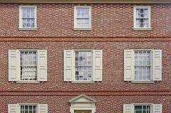 Alte Wand des roten Backsteins mit weißen Fensterläden Stockfotografie