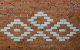 alte Wand des roten Backsteins mit weißer Verzierung Stockbild