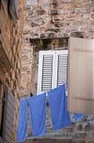 Alte Wand, Fenster und blaues Leinen (Italien) Stockfotos