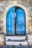 Alte Wand und blaue Holztür, Griechenland Stockfotografie