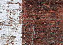 Alte Wandhälfte des roten Backsteins gemalt in der weißen Farbe Lizenzfreie Stockfotos