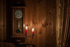 Alte Wanduhr und Kerzen Stockbild
