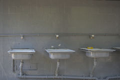 Alte Waschbecken auf einer grauen Wand Lizenzfreies Stockbild