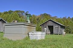 Alte Wasserpumpe, Badewanne und Maiskrippe Stockbild