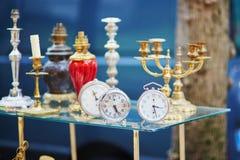 Alte Wecker und Kerzenhalter auf Flohmarkt in Paris Stockfotos