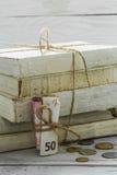 Alte Weißbüche mit Geld und Münzen auf hölzernem Hintergrund Lizenzfreies Stockbild