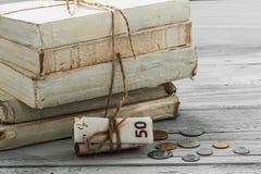 Alte Weißbüche mit Geld und Münzen auf hölzernem Hintergrund Stockfotos