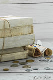 Alte Weißbüche mit Geld und Münzen auf hölzernem Hintergrund Stockbild