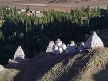 Alte weiße buddhistische stupas auf der Kante eines hohen Hügels im Ladakh-Tal, die Abendstrahlen der Sonne belichten die stupas Lizenzfreie Stockbilder