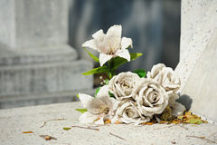 Alte weiße gefälschte Blume auf Grab Stockfotografie
