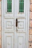 Alte weiße hölzerne Tür mit Openwork grünem Gitter als schönem Weinlesehintergrund Stockfoto