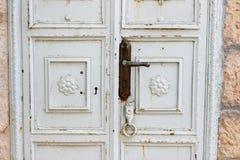 Alte weiße hölzerne Tür mit Openwork grünem Gitter als schönem Weinlesehintergrund Stockfotografie