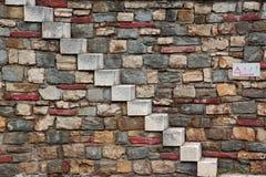 Alte weiße Steintreppe und mehrfarbige Steinmetzarbeit-Wand Lizenzfreie Stockbilder