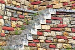 Alte weiße Steintreppe und mehrfarbige Steinmetzarbeit-Wand Stockfoto