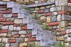 Alte weiße Steintreppe und mehrfarbige Steinmetzarbeit-Wand Stockbild